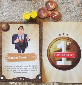 A character card, the starting player card, two yellow workers, and three coins.