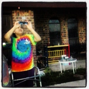 Noemi's daughter using a camera, her walker in front of her. She is wearing a tie-die shirt.
