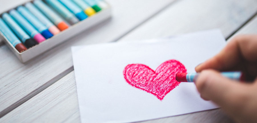 someone coloring a pink heart on a piece of paper using pastels. box of other colors in the distance