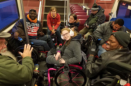 A young woman sits in a wheelchair in winter gear, in a subway car. She is surrounded by five others also bundled up on their way to a protest