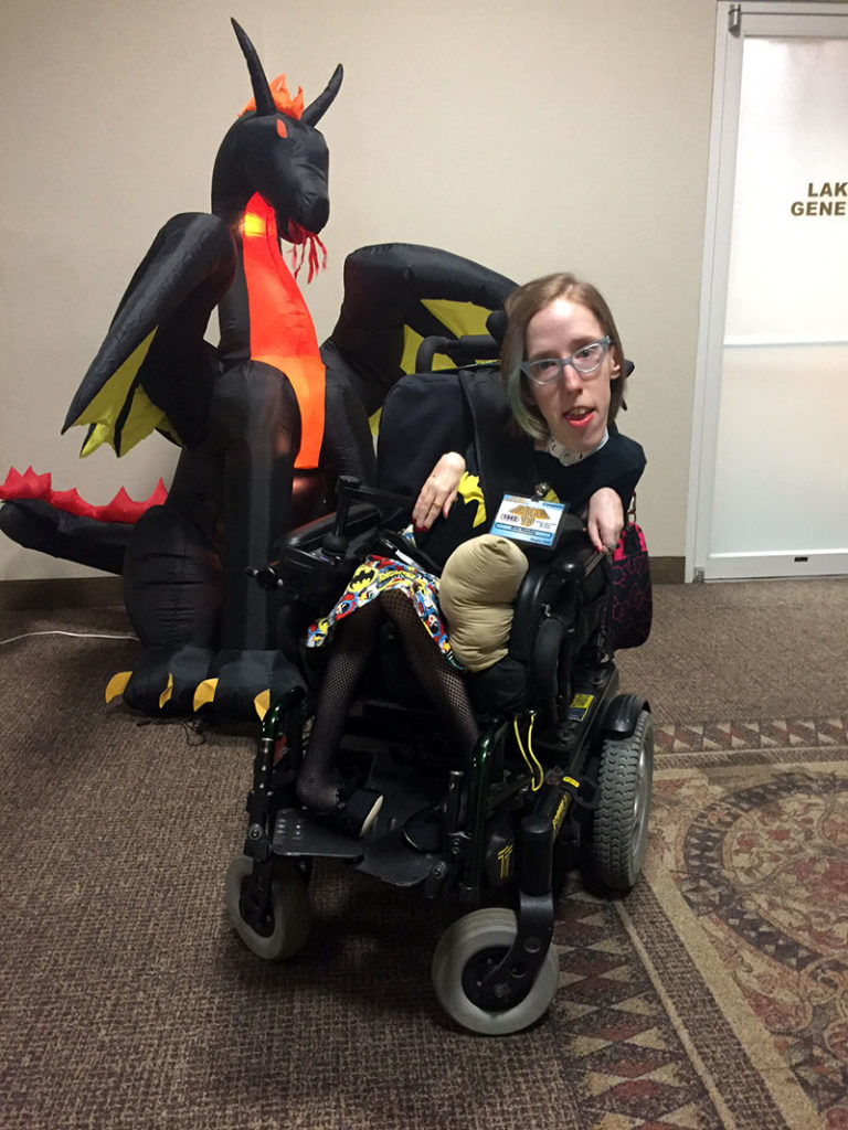 Me in my wheelchair in front of an inflatable dragon. I'm wearing a Batgirl shirt and skirt