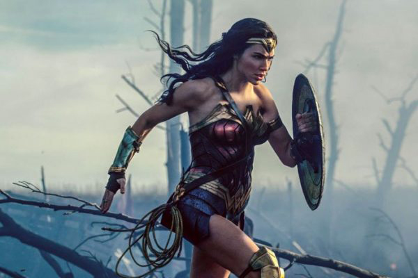 Wonder Woman in her costume, shield up and running, behind her is smoke and burned out trees
