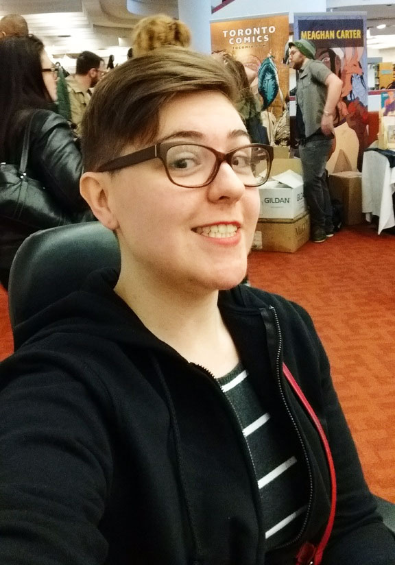 Woman with short hair and glasses sitting in a scooter at a convention hall