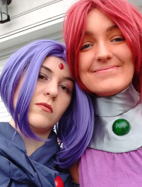 Elaine and her best friend dressed in costume. Elaine wears a purple wig, and dark robe.
