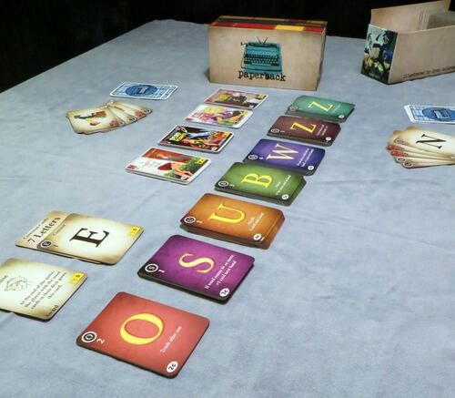 Cards with letters on them in decks, sprawling across the table.