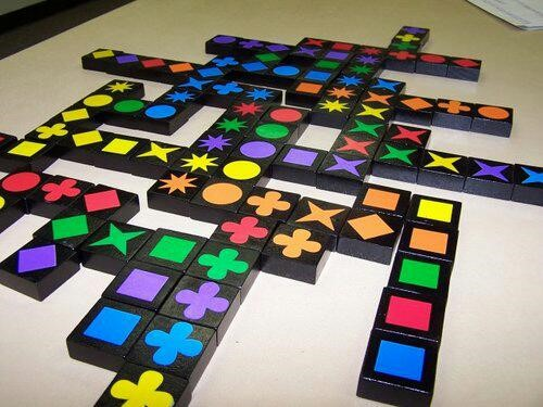 Multicolored square tiles with different colored shapes on them, set up like a Scrabble board