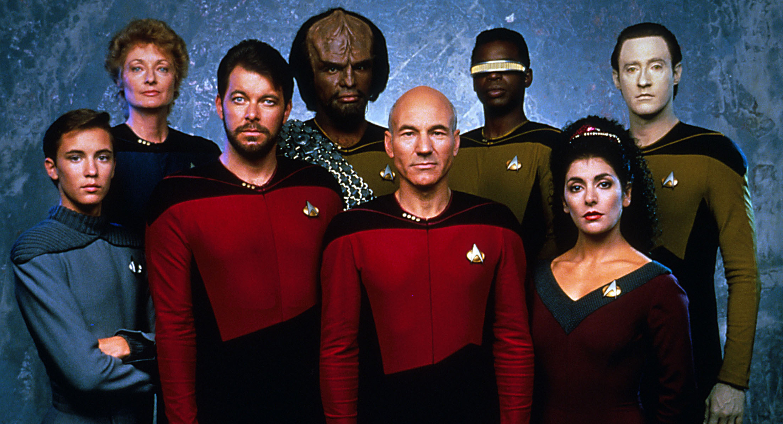 cast of Star Trek: The Next Generation standing in front of a blue background